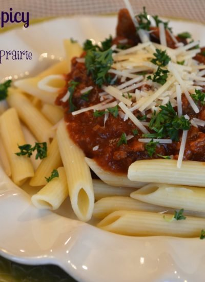 a white plate with penne noodles topped with beef in a tomato and cube steak sauce