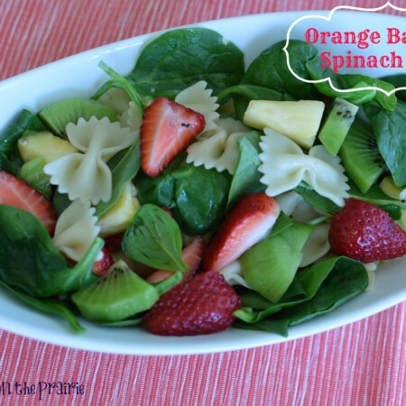 spinach salad with pasta, pineapple, strawberries in a white bowl