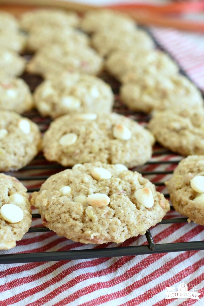 oatmeal cookies with white chocolate chip cookies on a cooling rack with a red and white cloth underneath