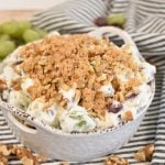 grape salad in a white dish topped with brown sugar and chopped walnuts