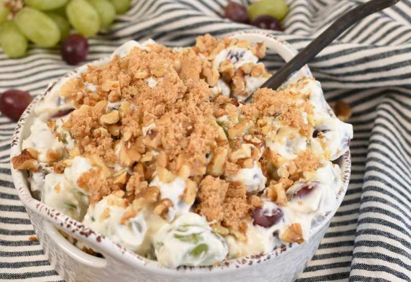 Grape salad in a white serving bowl with a black spoon on a black and white striped napkin with a bunch of green grapes in the backgroundl
