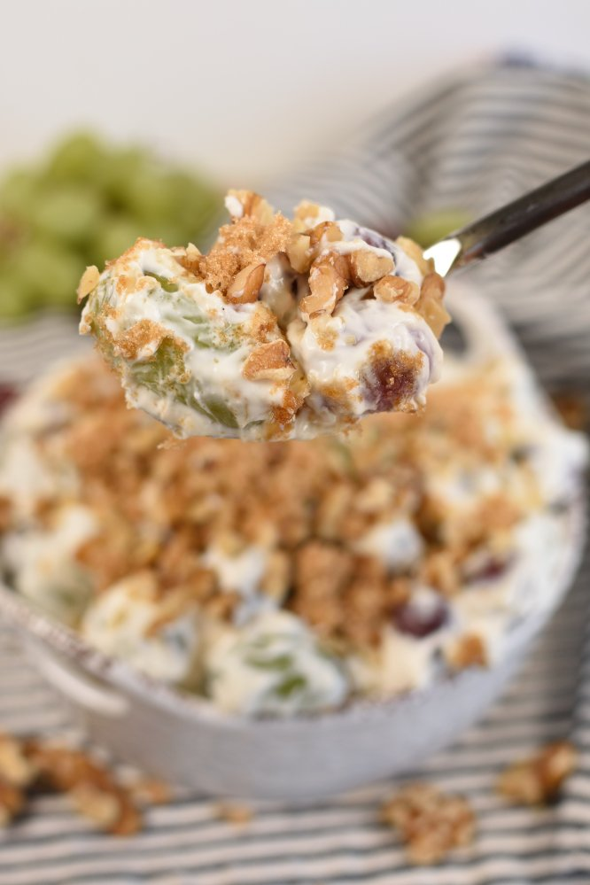 A serving spoon of grape salad with a blurred out image of a bowl of grape salad in the background