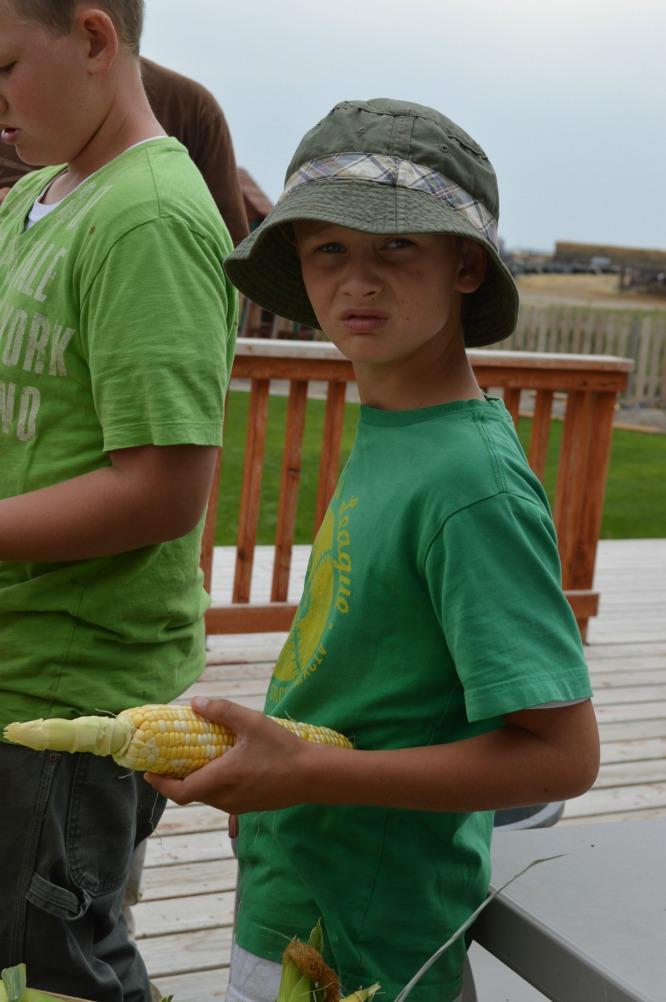 A boy husking a cob of corn