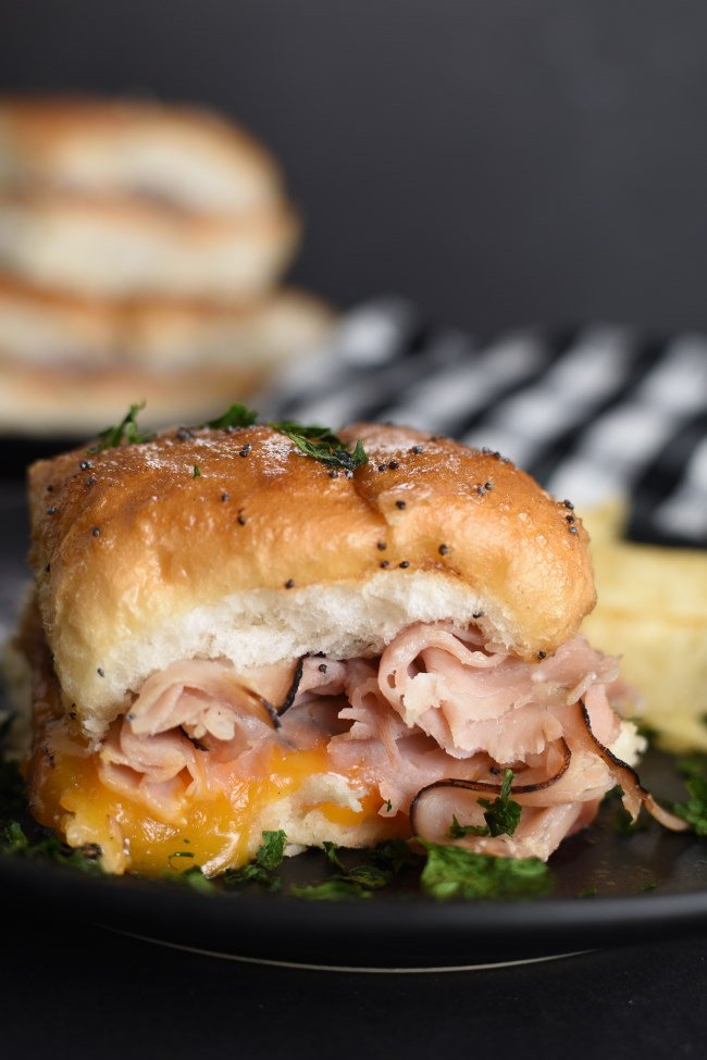 baked ham and cheese slider on a black plate