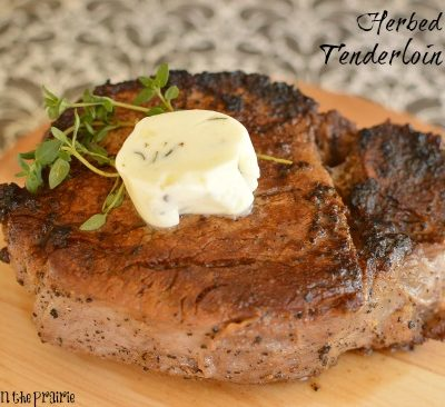 As seared tenderloin topped with a pat of butter and thyme on a wooden board