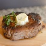A seared tenderloin topped with a pat of butter and thyme on a wooden board