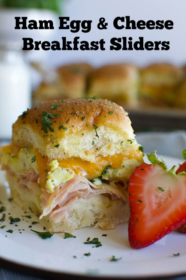 a white plate with a baked ham egg and cheese breakfast slider and a sliced strawberry