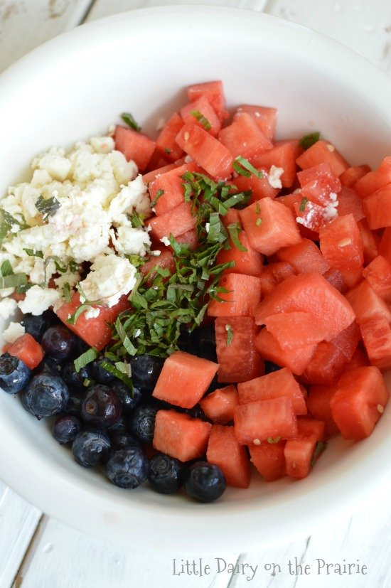 a white bowl with diced fresh watermelon, feta, blueberries, and mint no tossed together