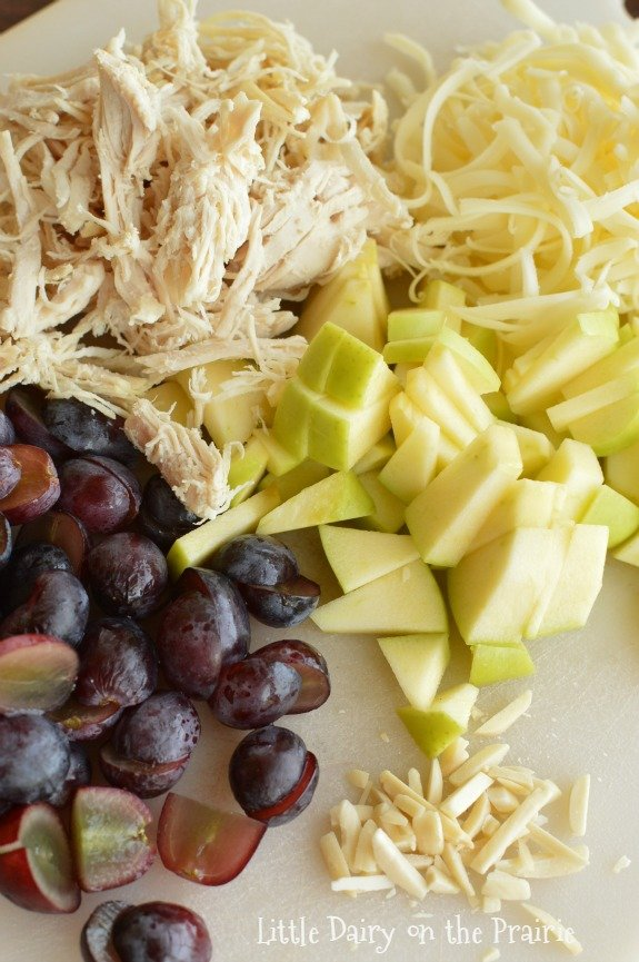 Chopped apples, shredded chicken, grated cheese, and red grapes.