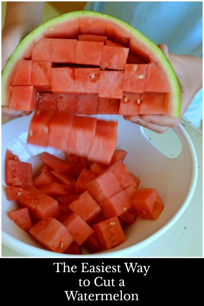 Red cubed watermelon falling from the rind into a white bowl