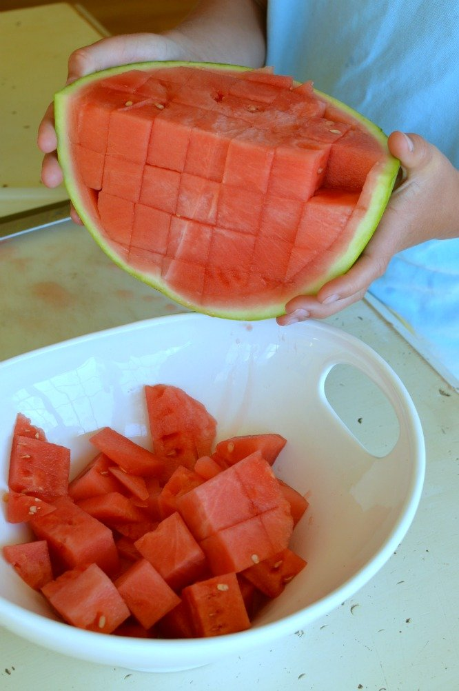 Pouring a quarter of a red cubed watermelon into a white bowl.