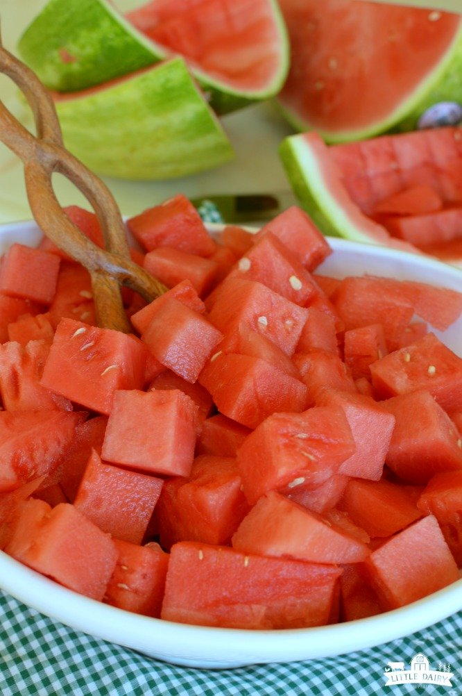 A white bowl of red cubed watermelon with a wooden spoon