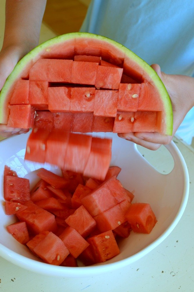 Dumping a cubed watermelon from the rind into a white bowl