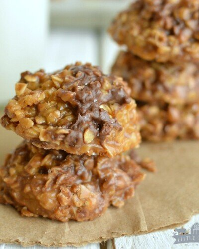 two no bake salted caramel cookies stacked on a paper with a jug of milk