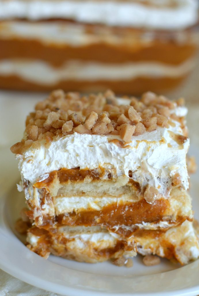 a pumpkin dessert with layers of pumpkin, graham crackers, and whipped cream, topped with toffee chips