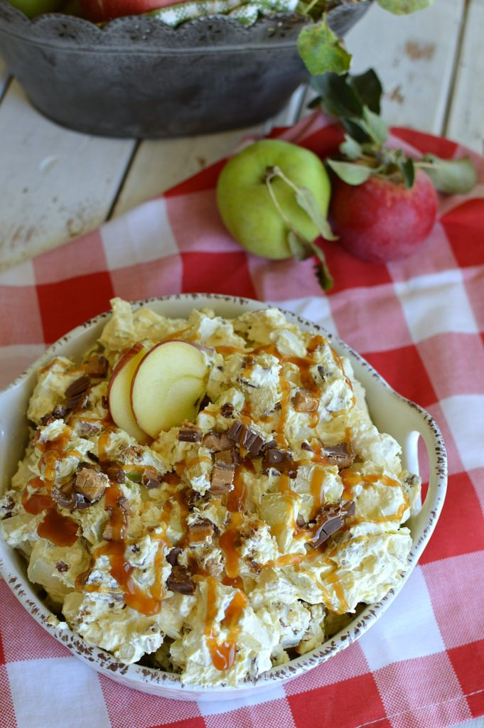 apple salad in a white dish drizzled with caramel ice cream topping