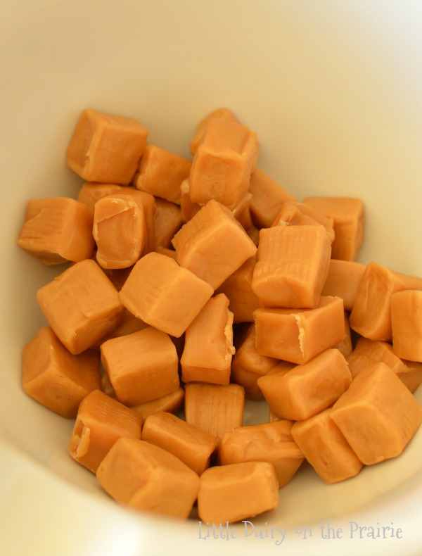Unwrapped caramel squares in a bowl.