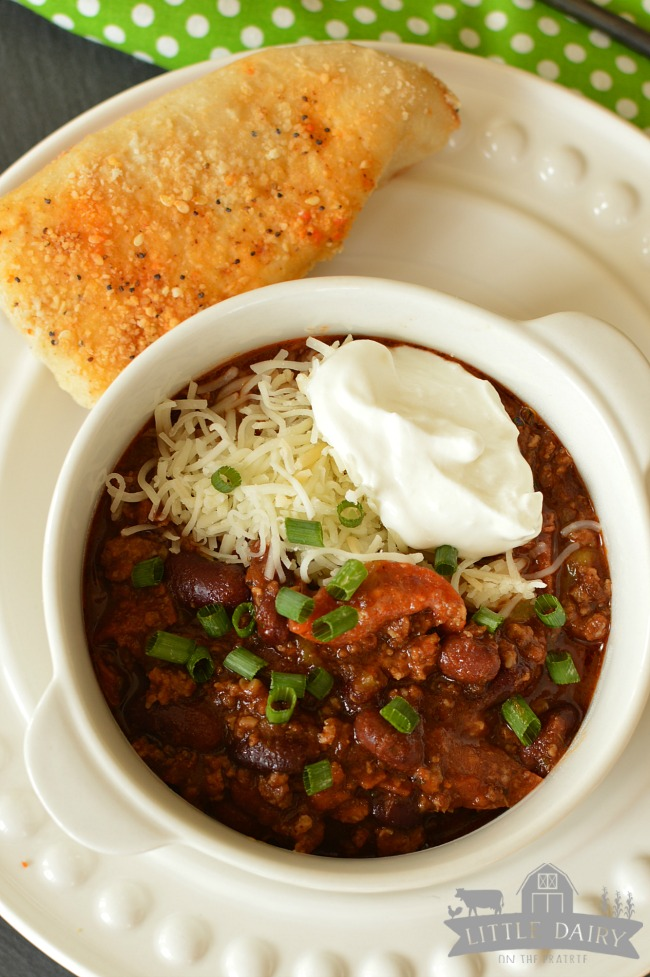 a bowl of chili topped with green onions, grated parmesan cheese, and sour cream