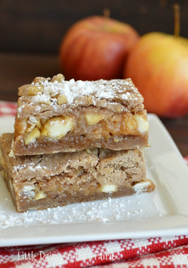two spiced blondies stacked on top of each other with apples in the background