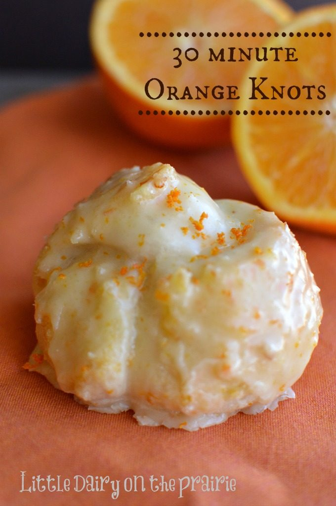 Orange knots glazed with icing, on an orange napkin with sliced oranges in the back