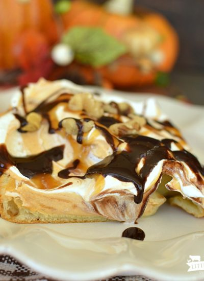 a square of dessert with a puff pastry crust, pumpkin cream layer, and topped with whipped topping, drizzled with caramel and hot fudge topping
