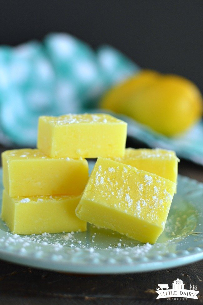 squares of bright yellow lemon fudge sprinkled with powdered sugar, on a light blue plate