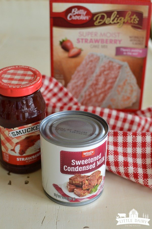 a can of sweetened condensed milk, a jar of strawberry sundae topping, and a cake mix