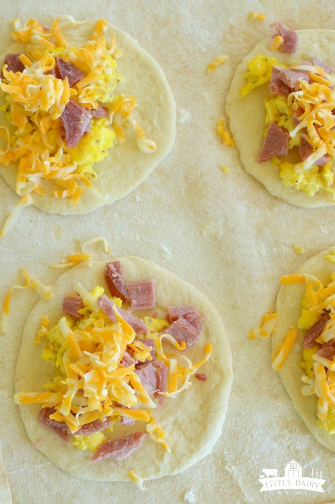 round piece of dough with eggs, ham, and cheese
