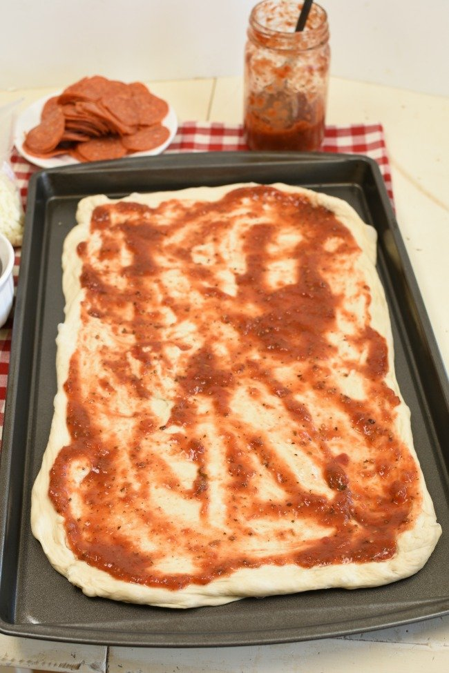 A cookie sheet with dough and marinara sauce spread over it.