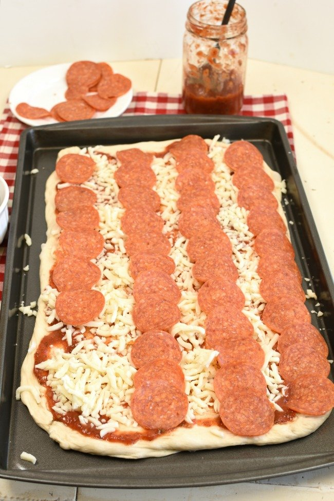 Flag pizza with stripes made with pepperoni slices.