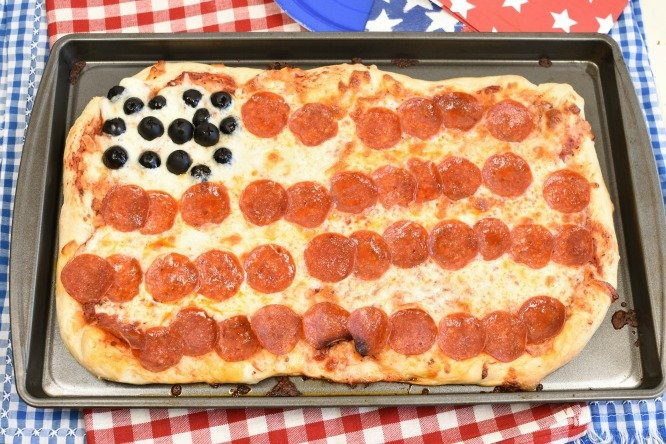 Pepperoni Pizza that looks like an American flag with olives.