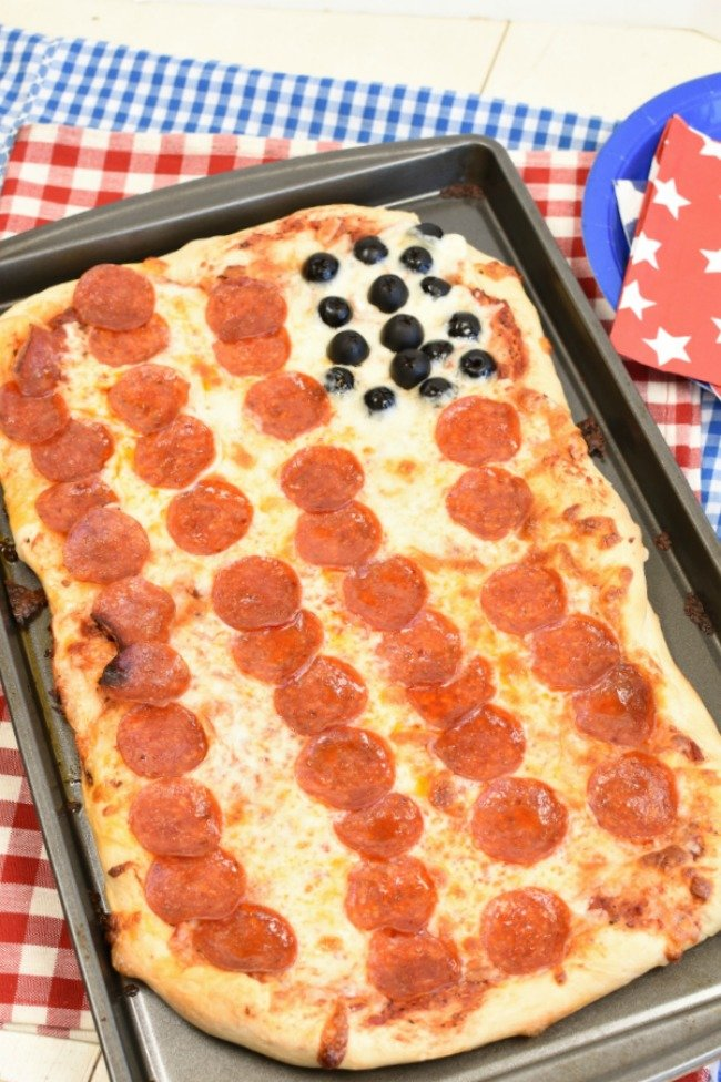 Pepperoni pizza that looks like and American flag with olives in the corner and sitting on a red and white and blue and white gingham table cloth.