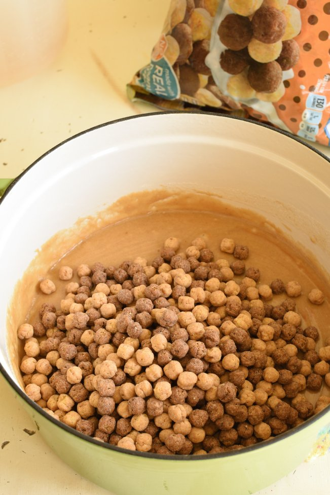 a white and green dutch oven pan with peanut butter mixture topped with cocoa and peanut butter puffs cereal