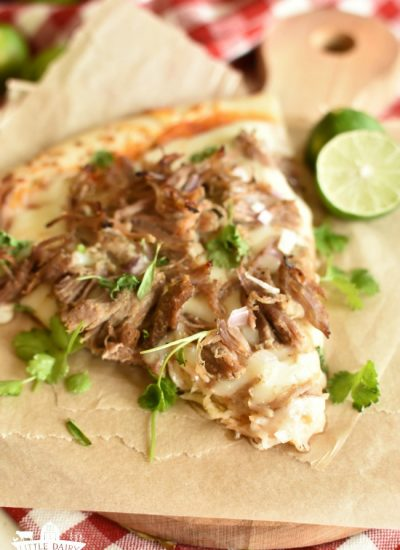a slice of pizza topped with shredded pork and cilantro on top of a brown paper and a lime half