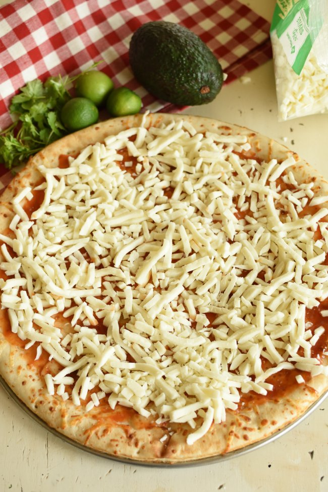 a flat bread crust topped with red sauce and grated white cheese