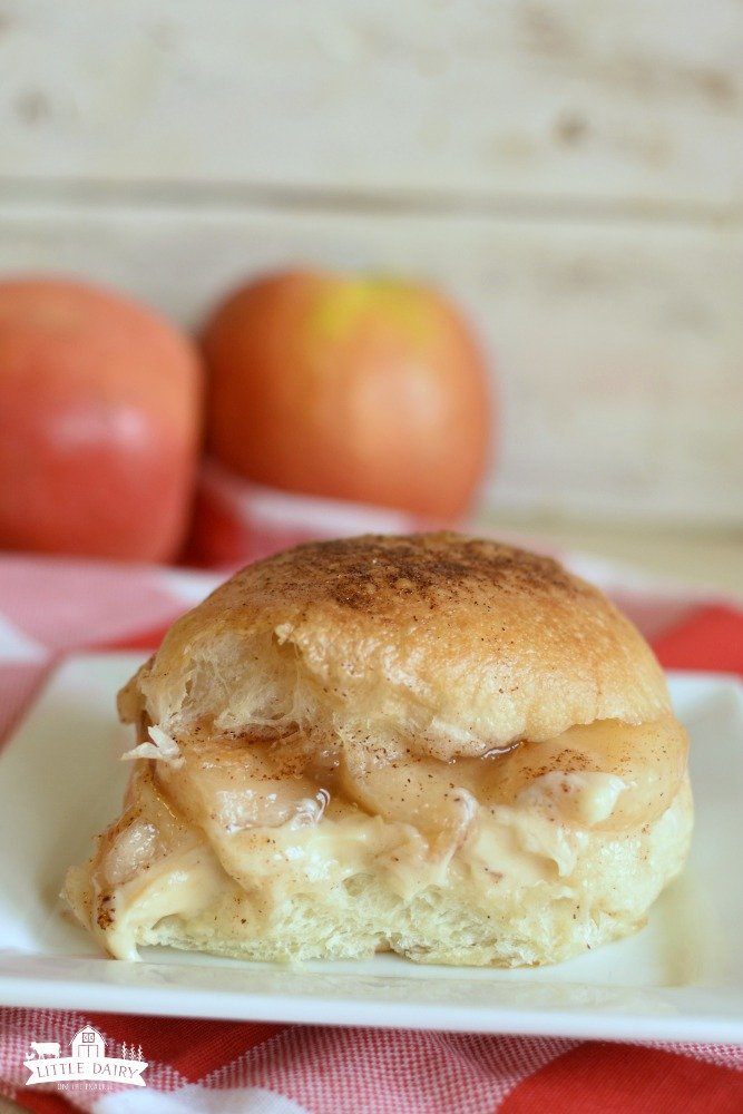 a white dinner roll with apple pie filling and cheesecake in the middle of it. The top of the roll is brushed with butter and sprinkled with cinnamon sugar.
