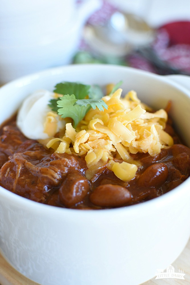 a close up image of chili topped with cheese and sour cream