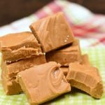 a stack of caramel candy squares on a green and white paper