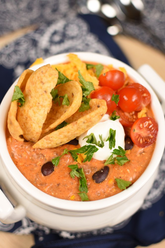 a white bowl with taco soup topped with corn chips, sliced cherry tomatoes, cilantro, and cilantro
