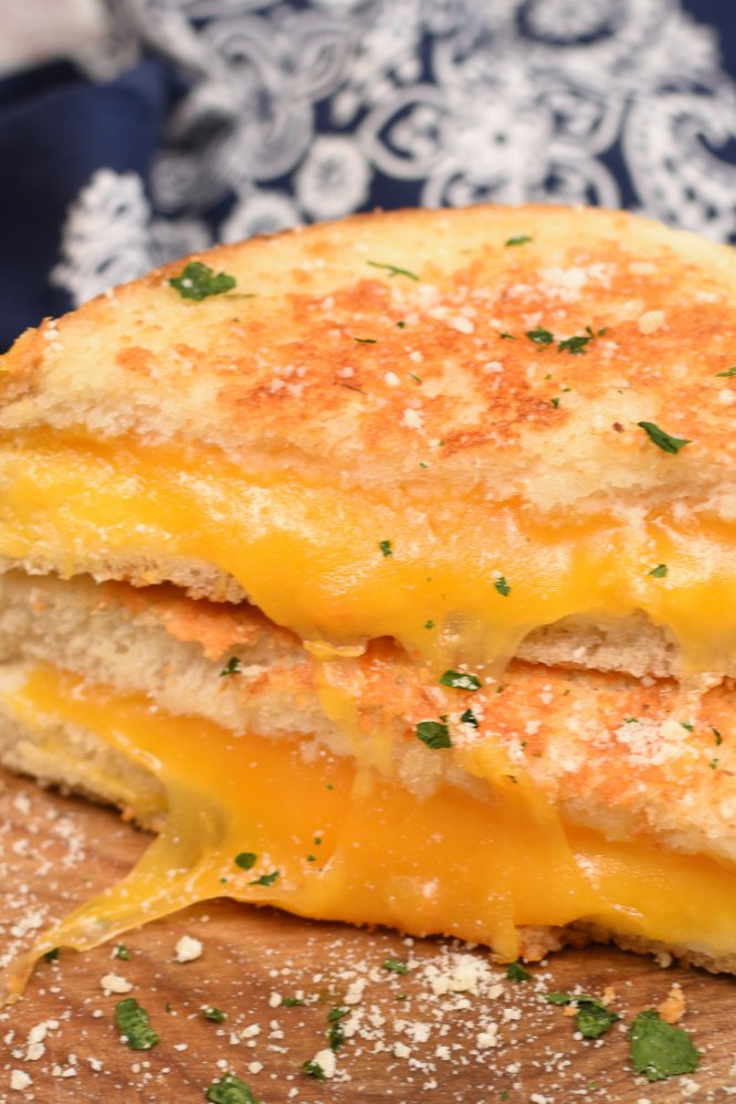 The only thing better than a toasty grilled cheese sandwich filled with gooey melted cheese on the inside, is a Parmesan Crusted Grilled Cheese Sandwich with the most incredible crispy garlic Parmesan crust on the outside! Today I'm beyond excited to share my Parmesan Grilled Cheese Sandwich with you guys! I've always been a HUGE lover of grilled cheese sandwiches because who could ever resist ooey gooey cheese nestled between golden brown buttery bread? Not me! Let me tell you though, the crust on my Parmesan Grilled Cheese Sandwich is so stinkin' divine! It's so good your going to sink back into your chair, close your eyes and fall in love! Something magical happens when you combine the soft melted cheese on the inside with that crispy, golden brown, buttery and cheesy crust on the outside! Well, by now you know that I married a dairy farmer and have lived on this stinky ol' farm for almost twenty years! I can't believe it's been that long since I agreed to live here with all these cows, flies, crazy hours, and pretty much be joined at the hip with this farm! After I met Justin and he told me he was a dairy farmer I think my heart sunk a little! He was a really great guy but I just didn't want to be married to a filthy dirty, no days off, muck boot wearing dairyman! Right after I decided my heart didn't need to be sunken I told him that I'd actually been supporting him for many, many years! I was convinced I was single handedly supporting the entire dairy industry with my love of cheese! I can pound more cheese in a month than most people can pound in a whole year. Surely Justin was getting his a portion of my hard earned money I spend on cheese! I'm seriously an addict. After I've been on vacation for a few days I start to really crave salty cheese! I add it to every single meal I make; pasta, scrambled eggs, cheese burgers, salads, mashed potatoes, and even pancakes (don't knock it till you try it, it's good)! I'll take cheese any way I can get it! But I have to