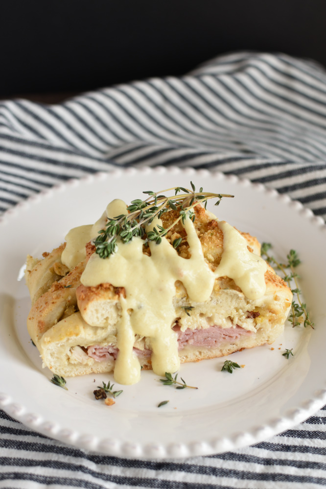 a baked bread braid filled with chicken and ham, drizzled with mustard sauce and sprinkled with thyme