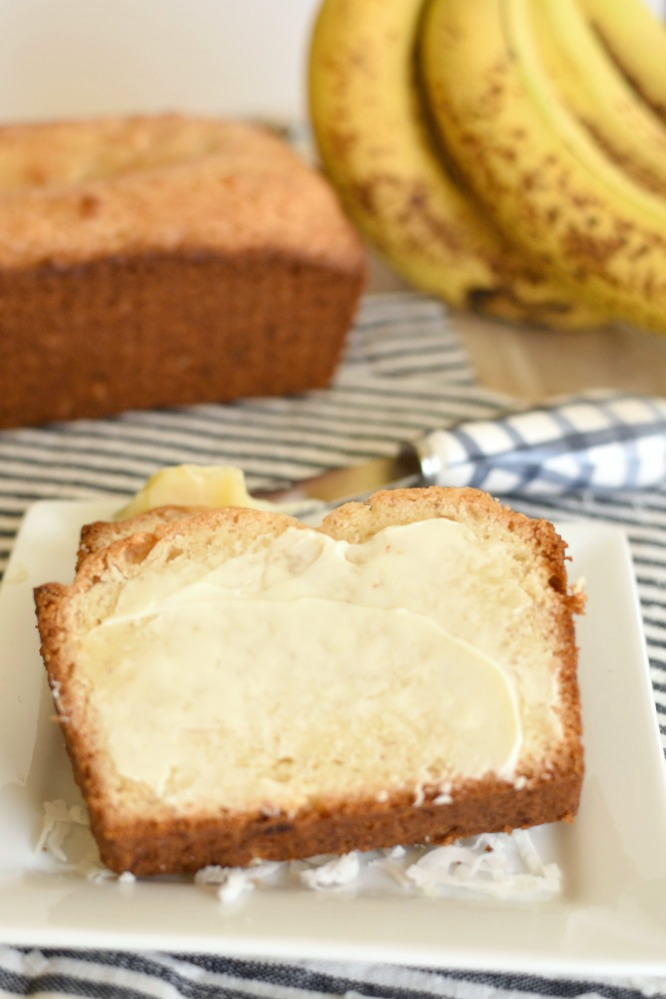 """Coconut Banana Bread is my new favorite go to banana bread recipe! It's a light quick bread that's perfectly sweetened! The addition of coconut brings the best flavor to this bread! One time when I was a kid my family visited a couple elderly friends of ours. They had a dish of candy on the end table, of course I wanted one. I politely sat there and eyed the candies until I couldn't help myself. I blurted out, """"Can I please have one of those?"""" My dad was horrified that I would ask our friends if I could have a candy. The candy was there's and I quickly remembered what I already know...you don't ask people if you can have something that belongs to them. Let's just say I got in trouble. Okay, it was big trouble and I never asked for anything again! A few years ago I went to visit my friend, Andra. Her house smelled amazing and she was just taking a couple loaves of Coconut Banana Bread out of the oven! Holy cow did I ever want her to share a slice of that warm bread with me! Of course I didn't ask her and I don't think I even sat there and eyed the bread. She must have read my mind, or maybe it's just because she's super nice, either way she offered me a slice of bread! Lucky me! That bread was amazing and I don't even like bananas! I've kept my love of her Coconut Banana Bread in the back of my mind, but since I don't like bananas I try not to keep them around! Justin and the kids don't go grocery shopping with me very often, so when they do they go hog wild adding all the junk I never buy. Junk like bananas, licorice, barbecue potato chips, and corndogs! The dang boys devoured all the licorice and barbecue chips and left the bananas on the countertop until they were overripe. Their crazy shopping spree now meant I had to take care of the overripe bananas! I've literally tired a million banana bread recipes (the boys buy bananas every single time they go shopping and never eat them, maybe they really don't like bananas just banana bread) over the years and this one i"""