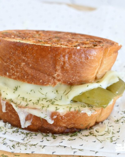 a toasted grilled cheese sandwich with melted provolone cheese and dill pickles