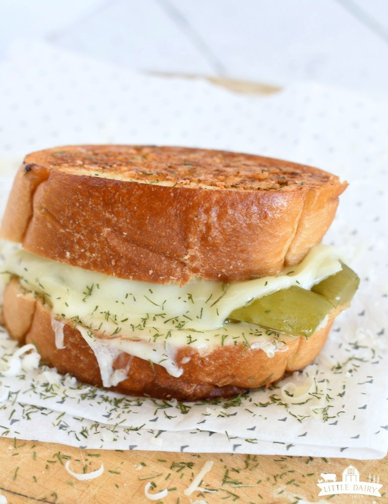 Dill Pickle Grilled Cheese Sandwich sitting on a paper with parmesan and grilled cheese sprinkled on the paper