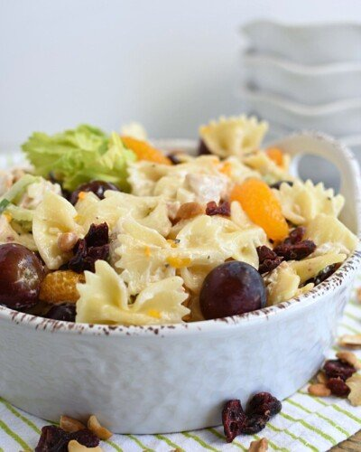a shallow white bowl filled with bow tie pasta, grapes, mandarin oranges coated in creamy dressing