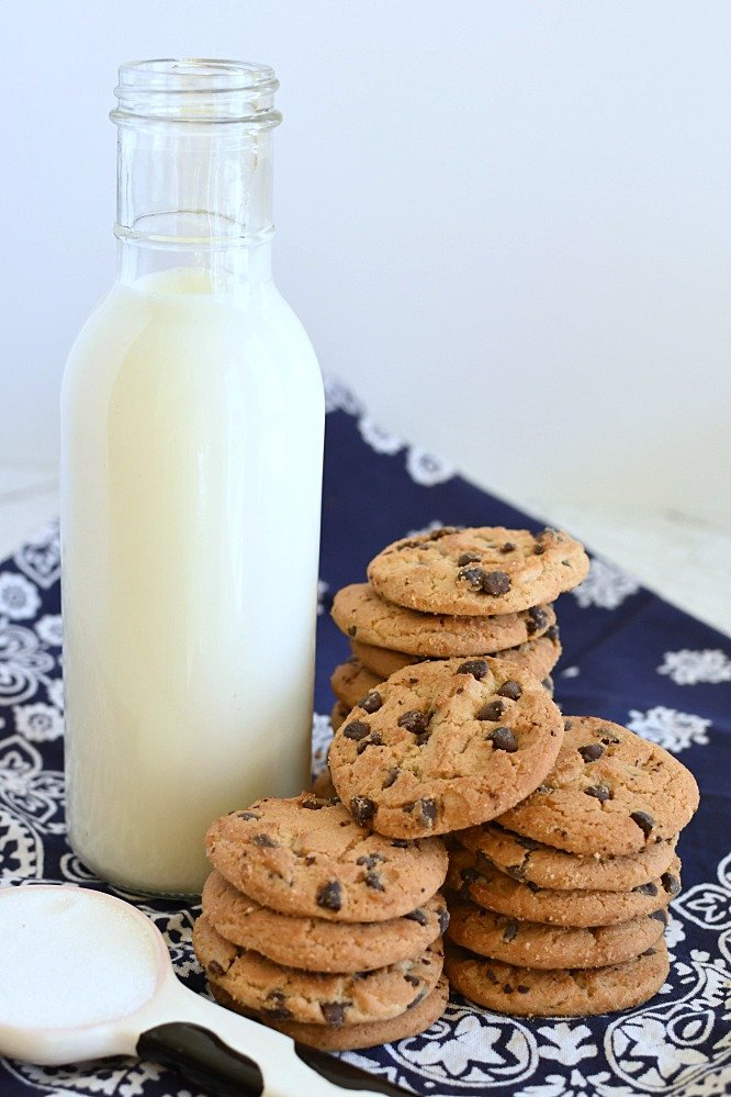 milk in a glass jar, a stack of chocolate chip cookies, and a tablespoon of sugar