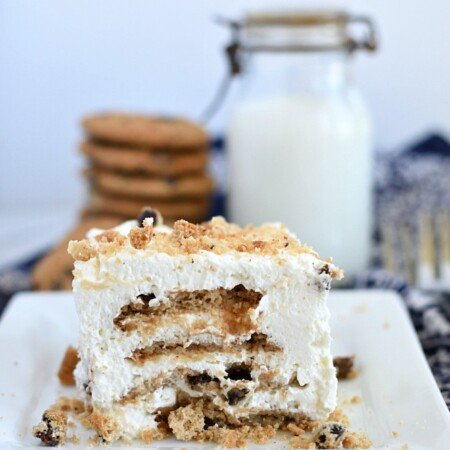 chocolate chip cookie ice box cake on a square white plate and a jar of milk with stacks of chocolate chip cookies
