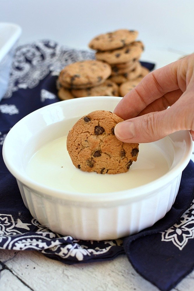 Fingers dunking a chocolate chip cookie into a white bowl of milk