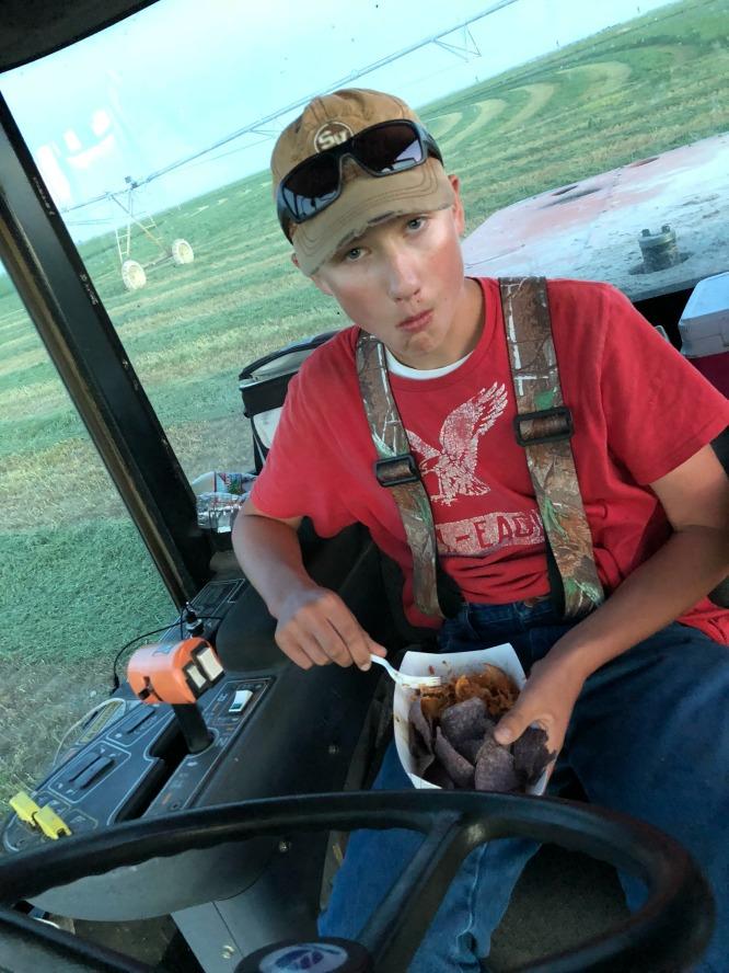 A boy in a red shirt sitting in farm equipment