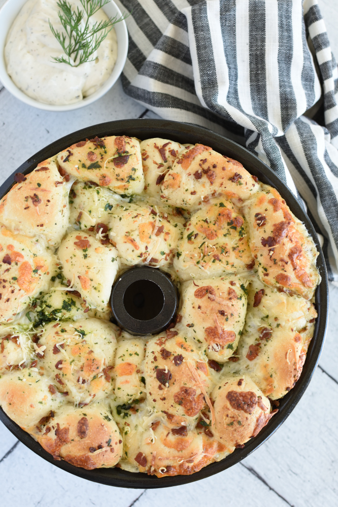 a bundt pan with baked monkey bread topped with cheese and parsely